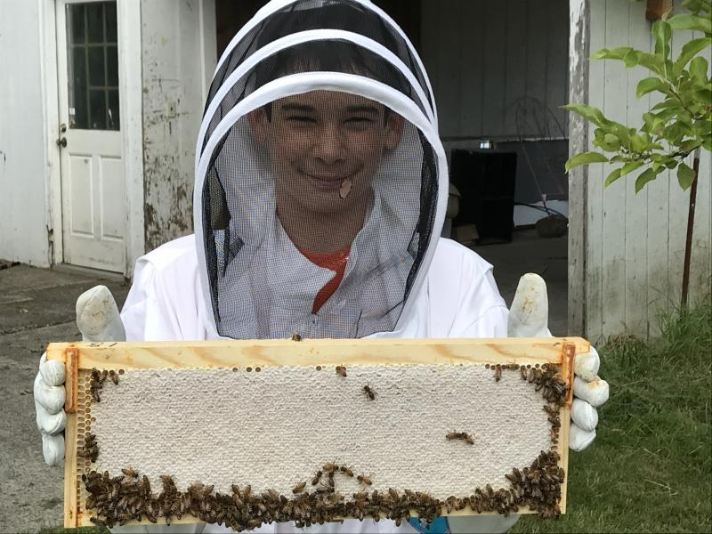 2018 Youth Scholar Austin with a frame of honey