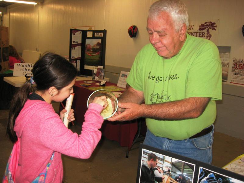 LCBA Mentor Gottfried Fritz shares raw honey with a young visitor to LCBAs Youth